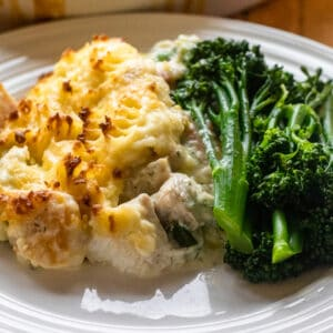 fish pie with cheesy mashed potato topping served with broccoli sprouts