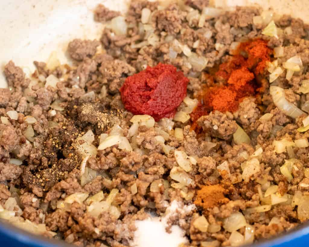Seasoning and tomato paste goes into meat sauce.