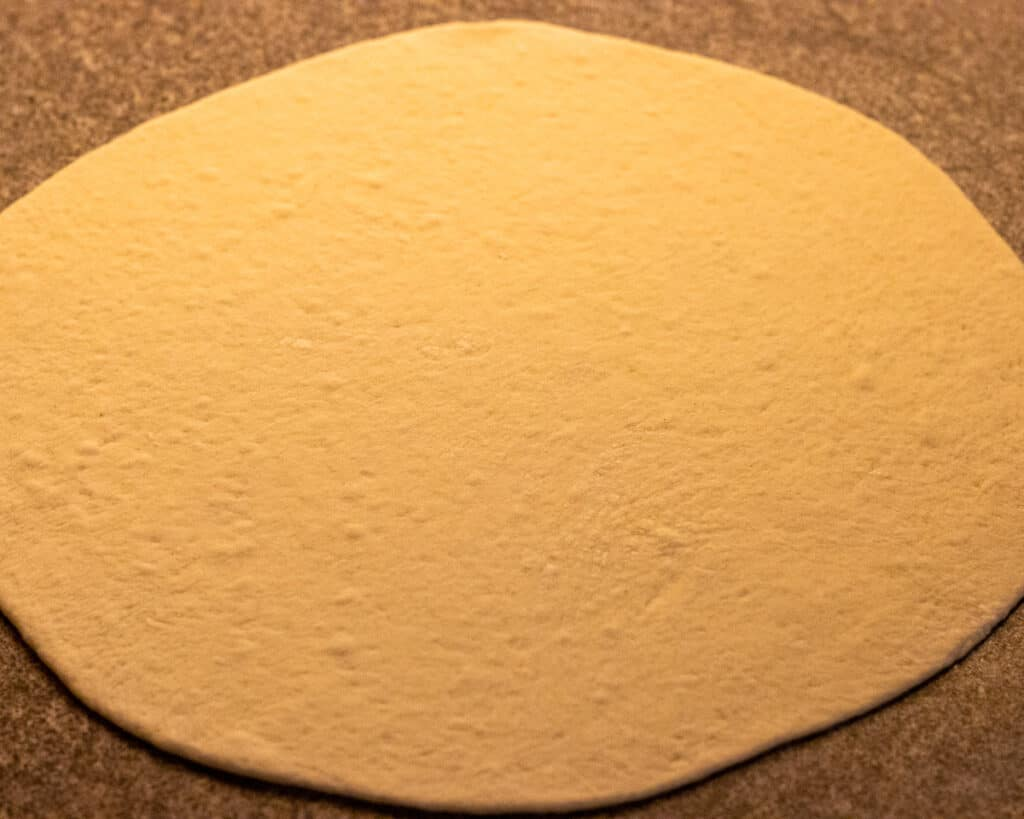 pita bread dough ball rolled out into a thin round pastry