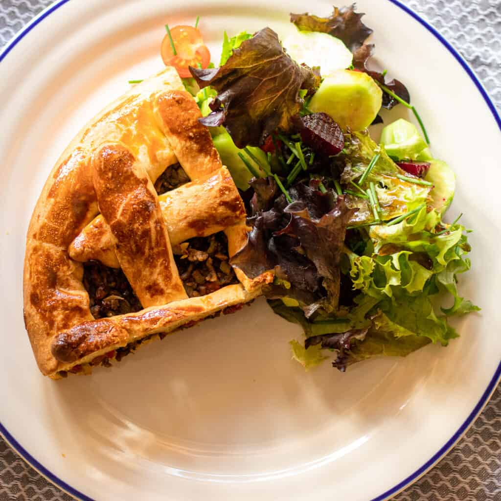 a slice of minced beef pie served with green salad