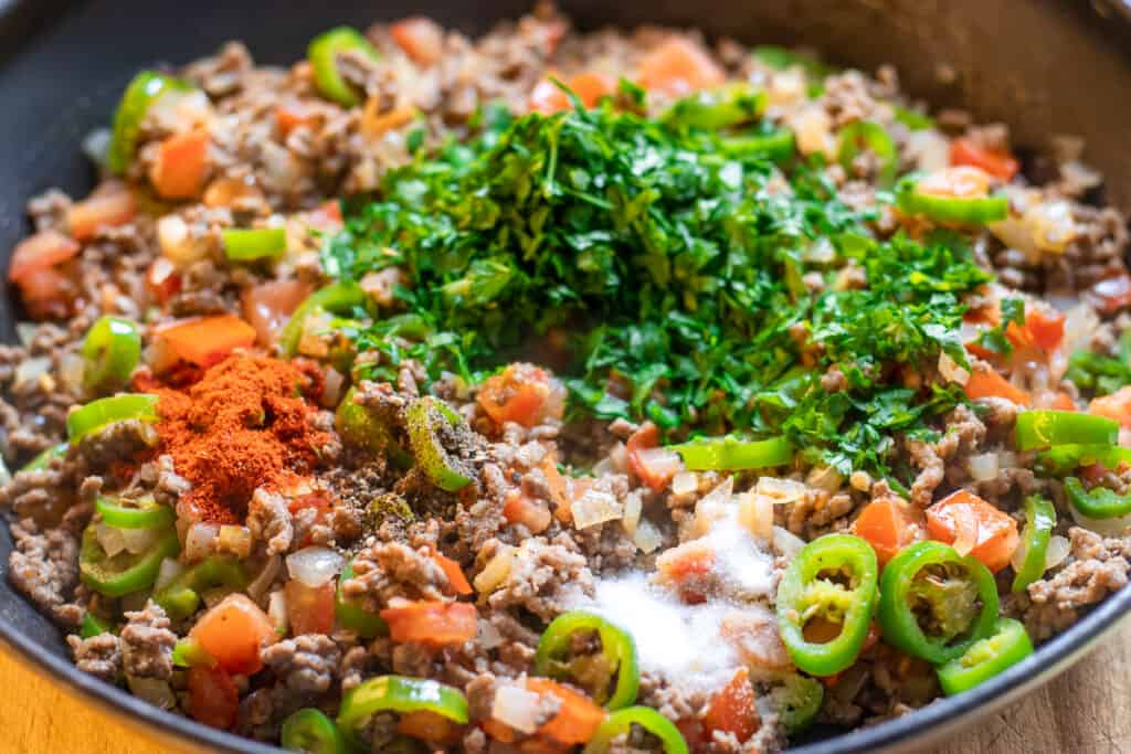 add tomatoes, spices and parsley to the minced beef pie mixture