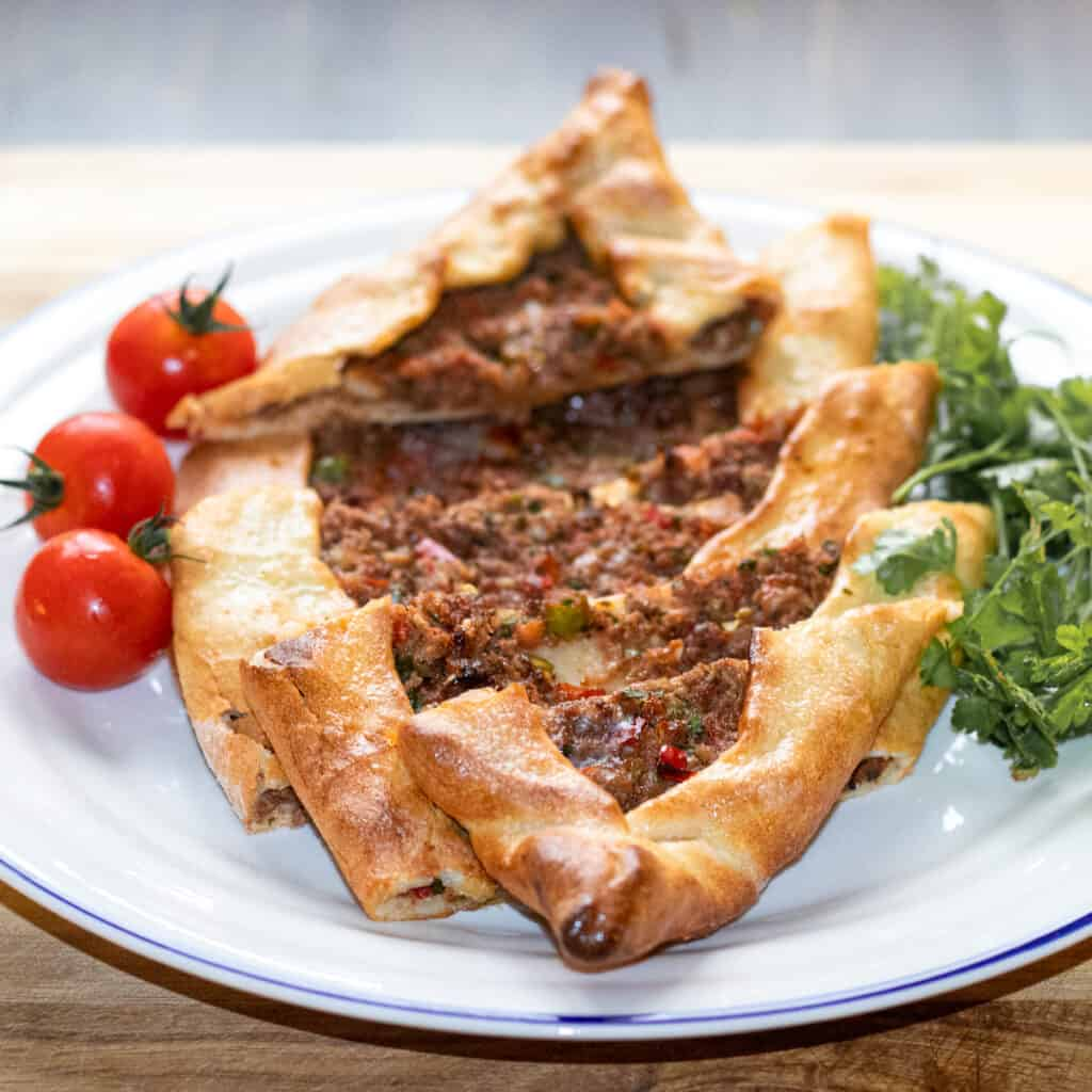 pide Turkish Kiymali Pide served with tomatoes and parsley
